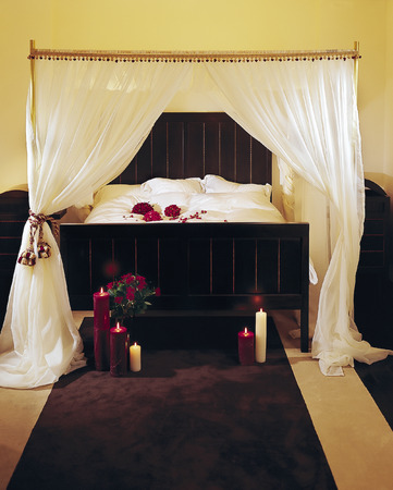 a fancy bed with a canopy,  candels and dried flowers Stock Photo - 1640015