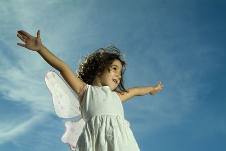young girl with fairy wings flying aginst blue sky with cirrus clouds photo