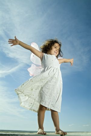 young girl with fairy wings flying aginst blue sky with cirrus clouds