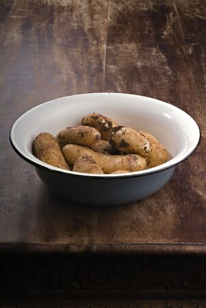 unwashed: dirty potatoes in an old bowl on a wooden table