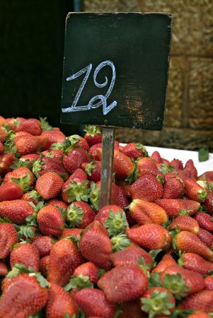 number 12: pile of  Strawberries in the market with a price sign with the number 12 Stock Photo