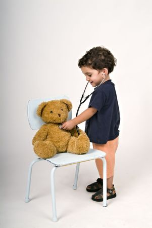 catarrh: boy doctor examining teddy bear Stock Photo