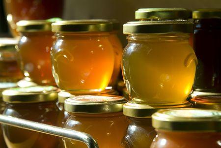 miel de abeja: muchos tarros de miel en un estante en un almac�n