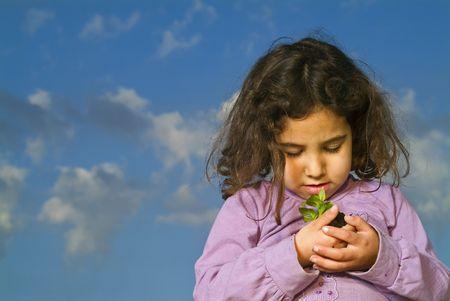 little girl holdinga plant against cludy blue sky Stock Photo - 2521149