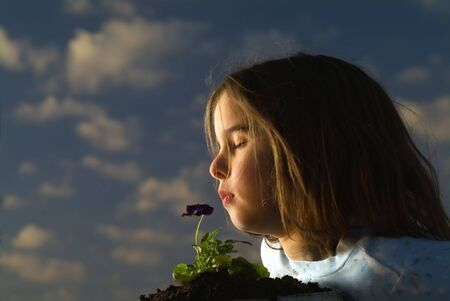 young girl smelling a pansy flower against cloudy sky photo