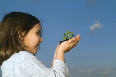 smilling child hands holding plant against clear blue sky Stock Photo - 2521150