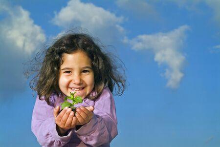 littel girl holding plant