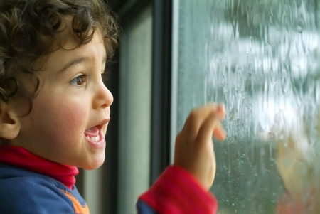 lloviendo: pequeño muchacho que mira la lluvia a través de la ventana Foto de archivo