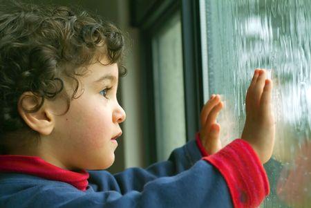 gotas de agua: Ni�o peque�o viendo la lluvia a trav�s de la ventana  Foto de archivo
