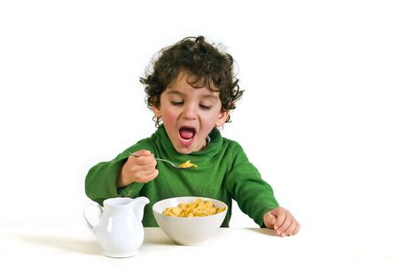 cornflakes: young boy eating cornflakes isolated on white Stock Photo