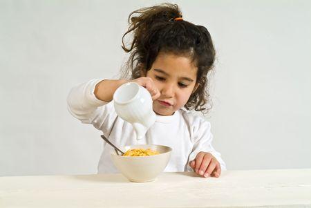 cereals: peque�a muchacha que sostiene una cuchara con los cereales Foto de archivo