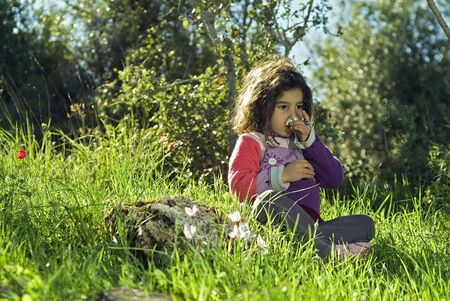 girl sitting in grass smelling a flower photo