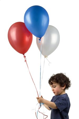 little boy holding 3 balloons
