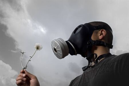 man with a gas mask holding a Dandelion photo