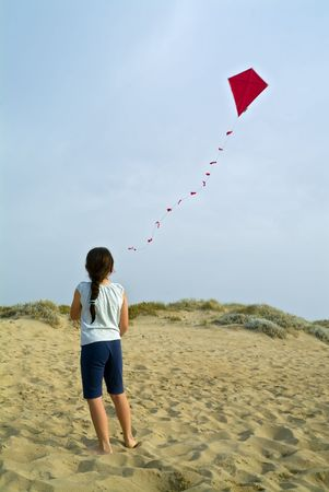 girl on beach playing with a red kite