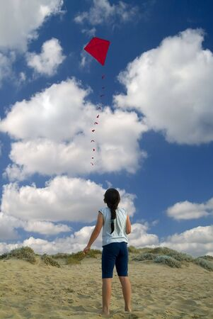 girl on beach playing with a red kite photo