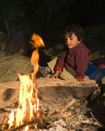 forest fire: boy sitting by the fire in a camp