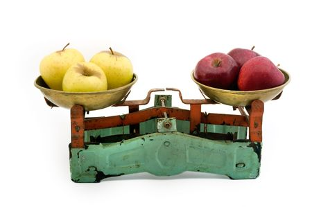 old scales with yellow and red apples isolated on white photo