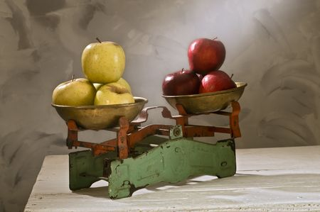 weighty: old scales with yellow and red apples isolated on white