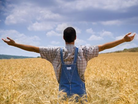 farmer standing in a wheat field with his arms spread out photo