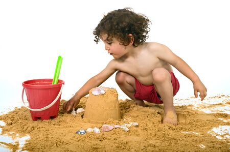 boy playing in the sand isolated on white photo