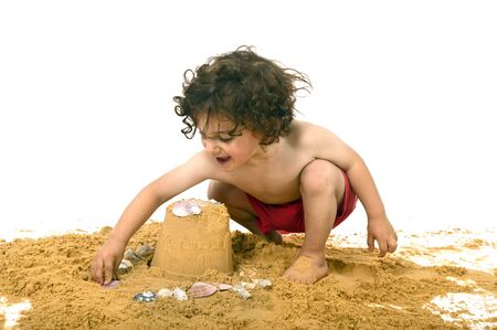 boy playing in the sand isolated on white