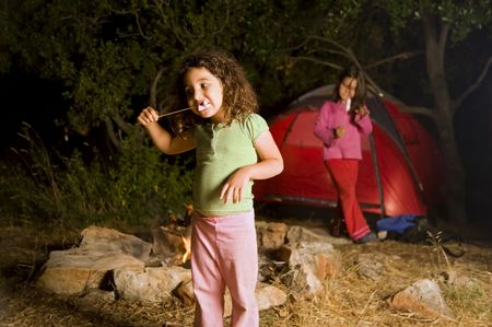 two girls at a camp eating marshmallow Stock Photo
