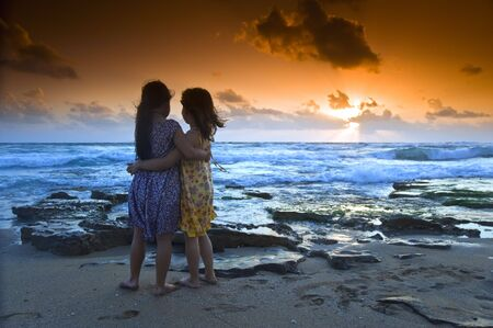 two girls in the beach at sunset