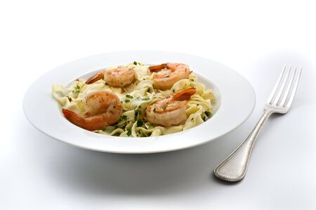 plate of pasta with shrimps and fork isolated on white photo