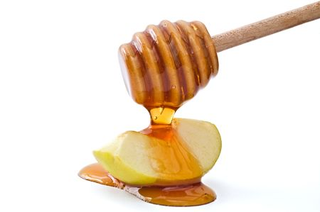 hashana: Honey drippin on a green apple slice isolated on white
