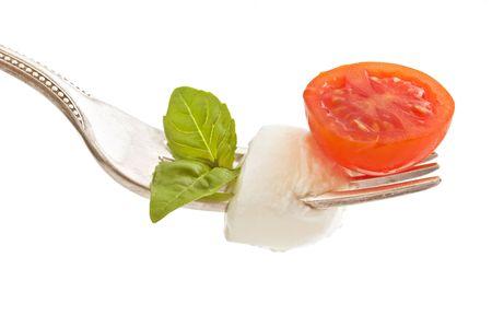 cherry tomato, mozzarella chess and basil leaf, forming the italian flag on fork isolated on white Stock Photo - 3271690
