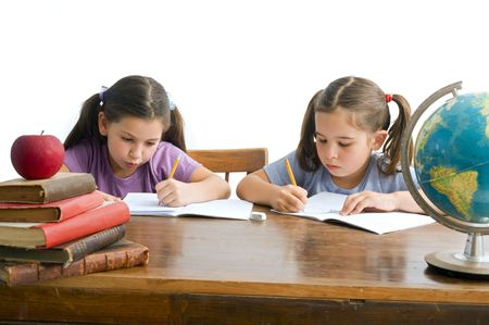 two girls pupils sitting by the table with globe and red apple on a pile of books, Isolated on white