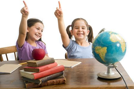 two girls pupels pointing in a class room with table, globe and red apple on a pile of books, Isolated on white photo