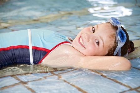 girl lying down: ni�a acostada en una piscina