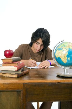 teenager boy sitting by his desk with a red apple on pile of books photo