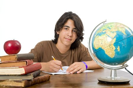 teenager boy sitting by his desk with a red apple on pile of books Stock Photo - 3323781