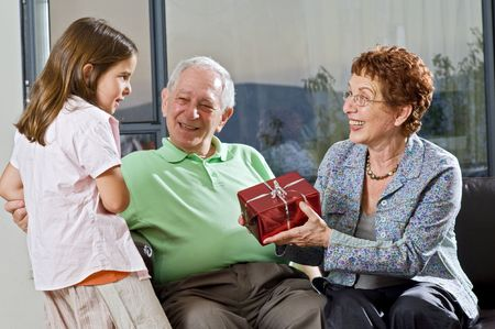 grandparents giving gift to grandchild at home Stock Photo - 3520894