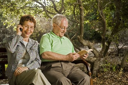 seniors couple sitting on a bench talking on the cell phone and reading in the park