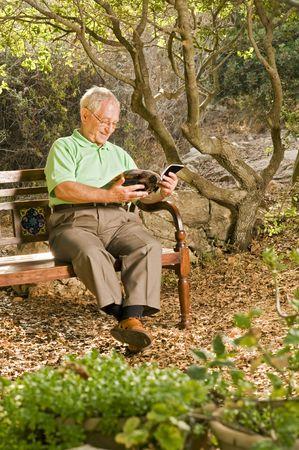 senior man reading on a bench