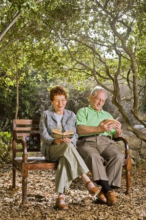 a year older: seniors couple sitting on a bench reading books in the park Stock Photo