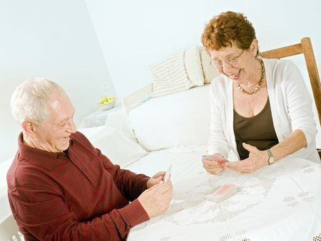 card player: senior couple having fun playing cards at home