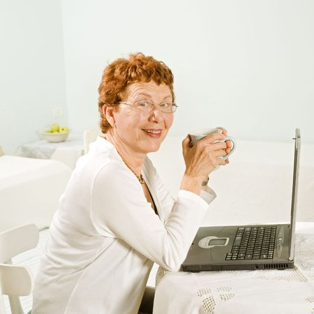 senior women and laptop computer at home