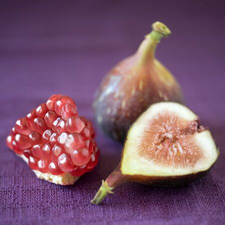 still life image of a part of pomgranate a whole fig and a slice of fig on purpule cloth