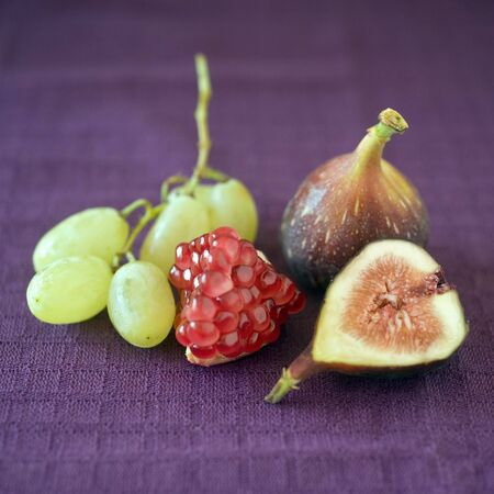purpule: still life image of a part of pomgranate, grapes, a whole fig and a slice of fig on purpule cloth