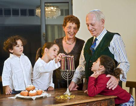 jewish home: grandperents and grandchildren lightening Hanukkiyah together