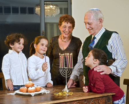 grandperents and grandchildren lightening Hanukkiyah together photo
