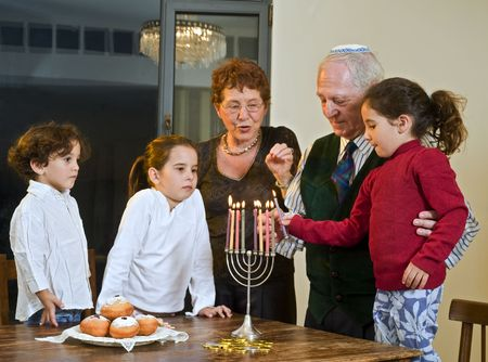 jewish home: grandperents and grandchildren lightening hannukia together