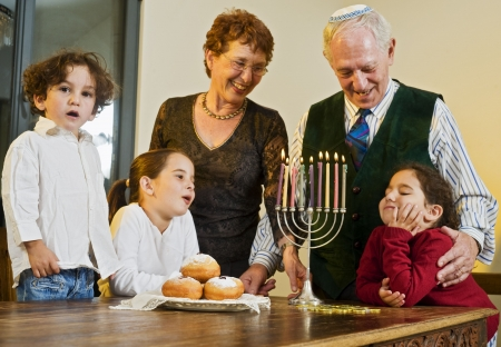 jewish home: grandperents and grandchildren lightening Hanukkiyah together
