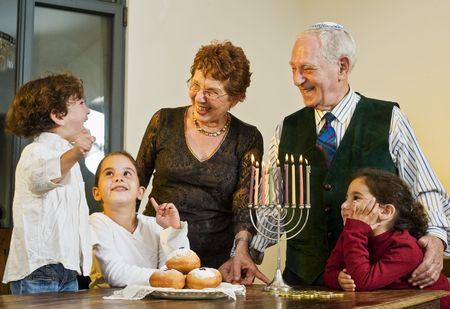 grandperents and grandchildren lightening Hanukkiyah together