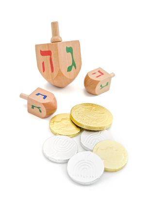 chanuka: three wooden dreidel and chocolate coins - gelt jewish hanukkah game isolated on white